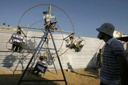 Palestinian children ride a Ferris wheel during a summer camp organised by the Hamas movement in Shati refugee camp in Gaza City June 22, 2009. (REUTERS/Suhaib Salem)