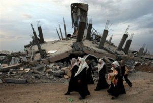 Palestinian women walk past a destroyed house in the Israeli-bombed Jabalia neighborhood. (AFP photo)